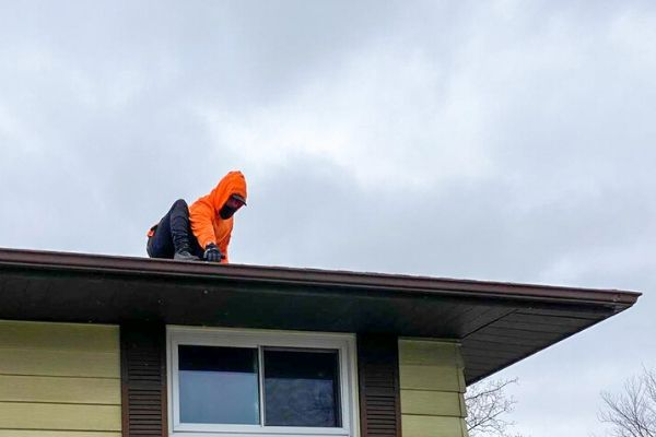 Employee checking gutters after removing the leaves and other debris.