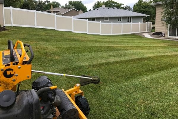 A yellow riding mower in a freashly cut sloping backyard