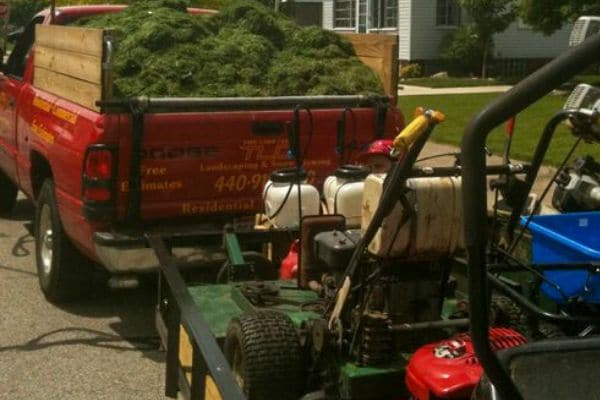 Truck with bed full of grass clipping pulling a trailer with lawn equipment.
